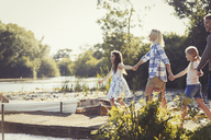 Family holding hands and walking on sunny lakeside dock - CAIF06078