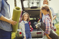 Portrait smiling girl with family unloading camping equipment from car - CAIF06081