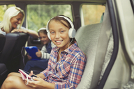 Portrait smiling girl with headphones using digital tablet in back seat of car - CAIF06084