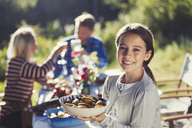 Portrait smiling girl serving food at sunny garden party patio table - CAIF06087