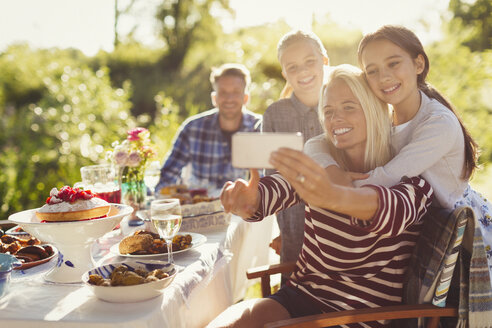 Mother and daughters taking selfie with camera phone at garden party patio table - CAIF06096