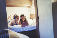 Sisters with headphones sharing digital tablet, watching video inside motor home - CAIF06105