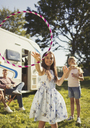 Portrait playful girl spinning plastic hoop outside sunny motor home - CAIF06111