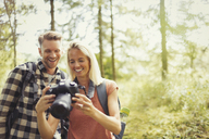 Smiling couple hiking, viewing digital SLR camera in woods - CAIF06114