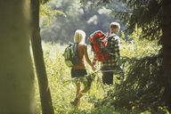 Couple with backpacks holding hands hiking in sunny woods - CAIF06117