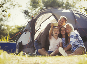 Family taking selfie with camera phone outside tent at sunny campsite - CAIF06120