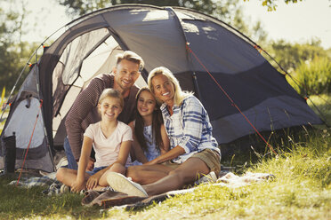 Portrait smiling family relaxing outside sunny campsite tent - CAIF06123