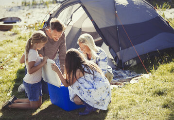 Family opening cooler outside sunny campsite tent - CAIF06129