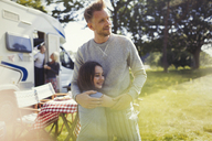 Affectionate father and daughter hugging outside sunny motor home - CAIF06132