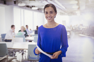 Portrait smiling businesswoman with paperwork in office - CAIF06150