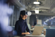 Businesswoman using virtual reality simulator at laptop in dark office - CAIF06189