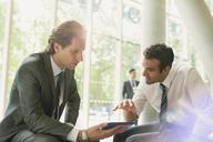 Businessmen meeting using digital tablet in office lobby - CAIF06201