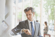 Businessman checking the time on wristwatch in office lobby - CAIF06204
