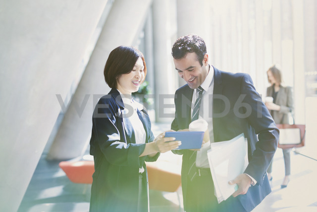 Businessman and businesswoman reviewing paperwork in sunny office lobby - CAIF06246 - Tom Merton/Westend61