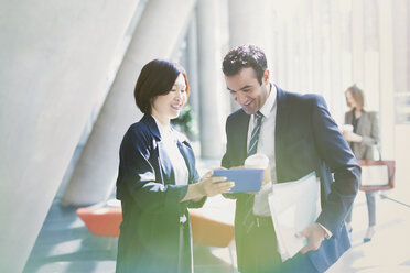 Businessman and businesswoman reviewing paperwork in sunny office lobby - CAIF06246