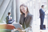 Smiling businesswoman using digital tablet in sunny office lobby - CAIF06249