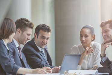 Business people using laptop in conference room meeting - CAIF06252