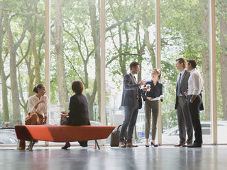 Business people talking in office lobby - CAIF06258