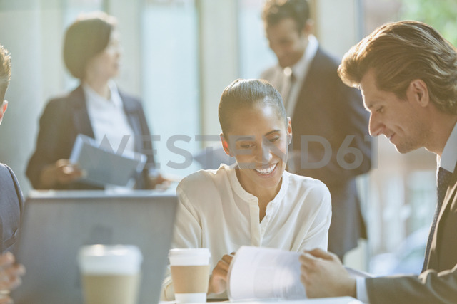 Businessman and businesswoman reviewing paperwork in conference room meeting - CAIF06264 - Tom Merton/Westend61