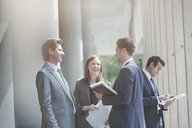 Business people talking and laughing in sunny office lobby - CAIF06267