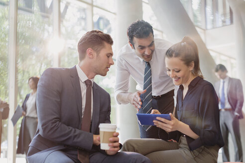 Business people with coffee using digital tablet, talking in office lobby - CAIF06273