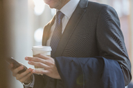 Close up businessman in suit with coffee texting with cell phone - CAIF06276