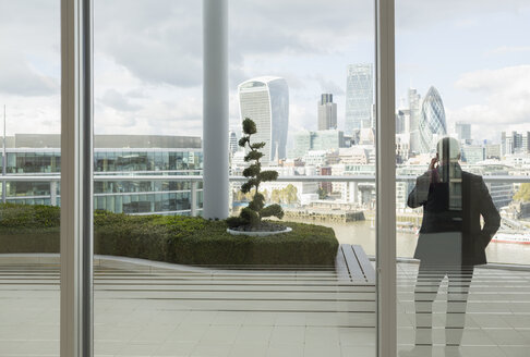 Businessman talking on cell phone on balcony with urban city view, London, UK - CAIF06282