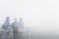 Business people talking and drinking coffee on foggy urban balcony - CAIF06285