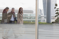 Business people walking on urban highrise balcony - CAIF06294