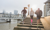 Runners running up sunny urban waterfront steps - CAIF06303