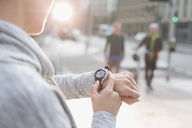 Female runner checking smart watch on urban street - CAIF06318