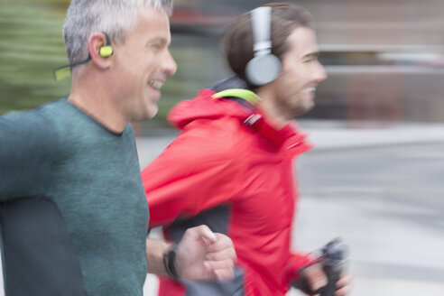 Smiling male runners with headphones running - CAIF06327