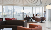 Business people clapping for businesswoman leading meeting in highrise urban lounge - CAIF06330