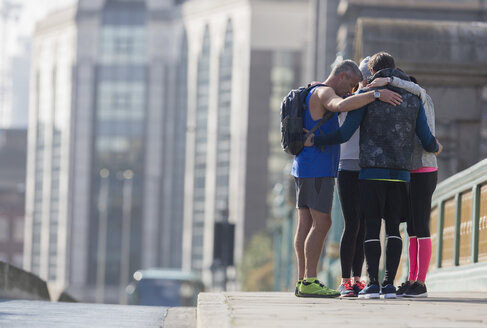 Runners connected in a huddle on sunny urban sidewalk - CAIF06333