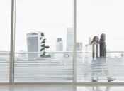 Businessman and businesswoman walking on urban highrise balcony with city view - CAIF06342