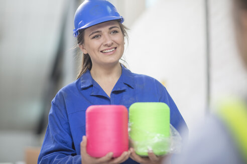Portrait of smiling woman wearing hard hat holding spools in factory - ZEF15120
