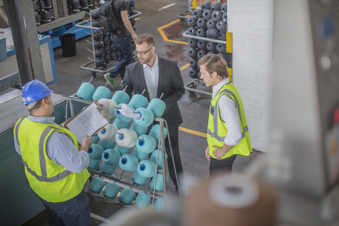 Businessman and staff checking delivery in factory - ZEF15132