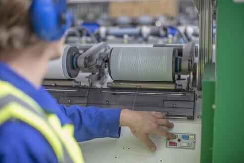 Man wearing ear defenders operating spool machine in factory - ZEF15159