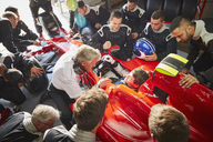 Manager and pit crew surrounding formula one driver in race car - CAIF06368