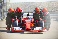 Pit crew pushing formula one race car out of pit lane - CAIF06374