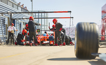 Pit crew working on formula one race car in pit lane - CAIF06380