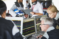 Formula one team reviewing diagnostics telemetry data on computers - CAIF06389