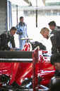 Formula one driver watching pit crew working on race car in repair garage - CAIF06395