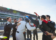 Formula one driver and racing team celebrating victory on sports track - CAIF06407