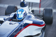 Formula one race car driver in helmet on sports track - CAIF06413