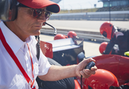 Manager with stopwatch timing formula one pit stop practice session - CAIF06419