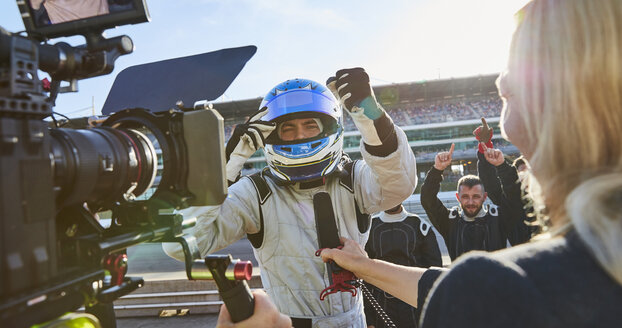 News reporter and cameraman interviewing formula one driver cheering, celebrating victory - CAIF06428