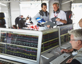 Formula one racing team reviewing diagnostics on computers in repair garage - CAIF06437