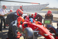 Pit crew replacing tires on formula one race car in pit lane practice session - CAIF06440