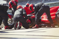 Pit crew replacing tires on formula one race car in pit lane - CAIF06464